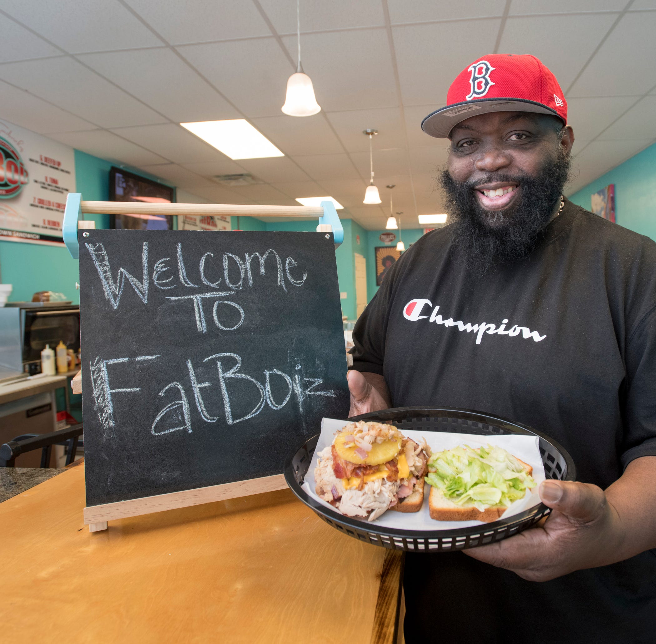 Owner Moses Williams shows off the stack of food inside the Hawaiian Club at Fatboiz sandwich shop on North Pace Blvd. in Pensacola on Tuesday, March 19, 2019.