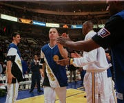 Golden State Warriors forward Chris Mullin, center, is introduced before the Warriors' game against the Boston Celtics Wednesday night, Feb. 19, 1997, at the San Jose, Calif., Arena.  Mullin tied the Warriors' Nate Thurmond for his 757th record game as a Warrior.  Mullin is also in the middle of a trade rumor.  (AP Photo/Paul Sakuma)