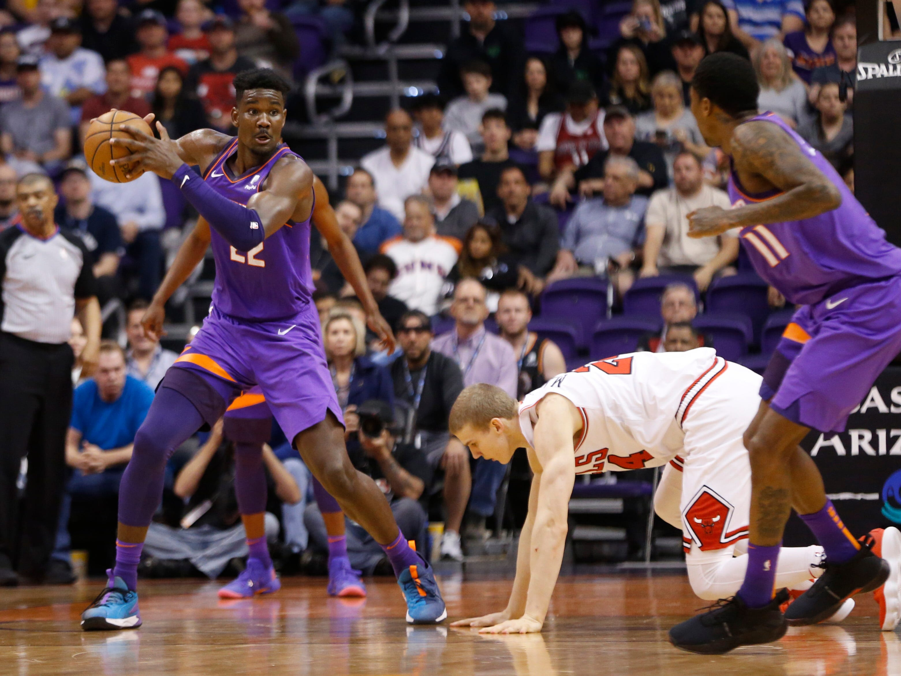 Suns' Deandre Ayton (22) recovers a steal against Bulls' Lauri Markkanen (24) during the first half at Talking Stick Resort Arena in Phoenix, Ariz. on March 18, 2019.