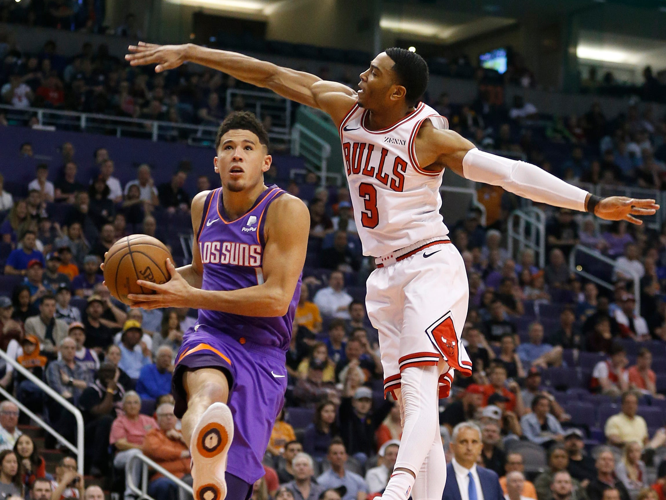 Suns' Devin Booker (1) goes underneath the defense of Bulls' Shaq Harrison (3) during the second half at Talking Stick Resort Arena in Phoenix, Ariz. on March 18, 2019.