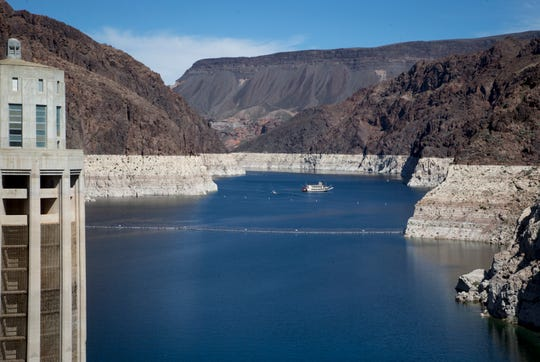 """The Desert Princess, a three-level paddle-wheeler, cruises past Rock Island, March 17, 2019, in the Lake Mead National Recreation Area near the Arizona/Nevada border. A high-water mark or """"bathtub ring"""" is visible on the island; Lake Mead is down 139 vertical feet."""