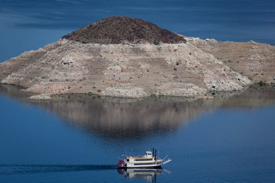 "The Desert Princess, a three-level paddle-wheeler, cruises past Rock Island, March 17, 2019, in the Lake Mead National Recreation Area near the Arizona/Nevada border. A high-water mark or ""bathtub ring"" is visible on the island; Lake Mead is down 139 vertical feet."