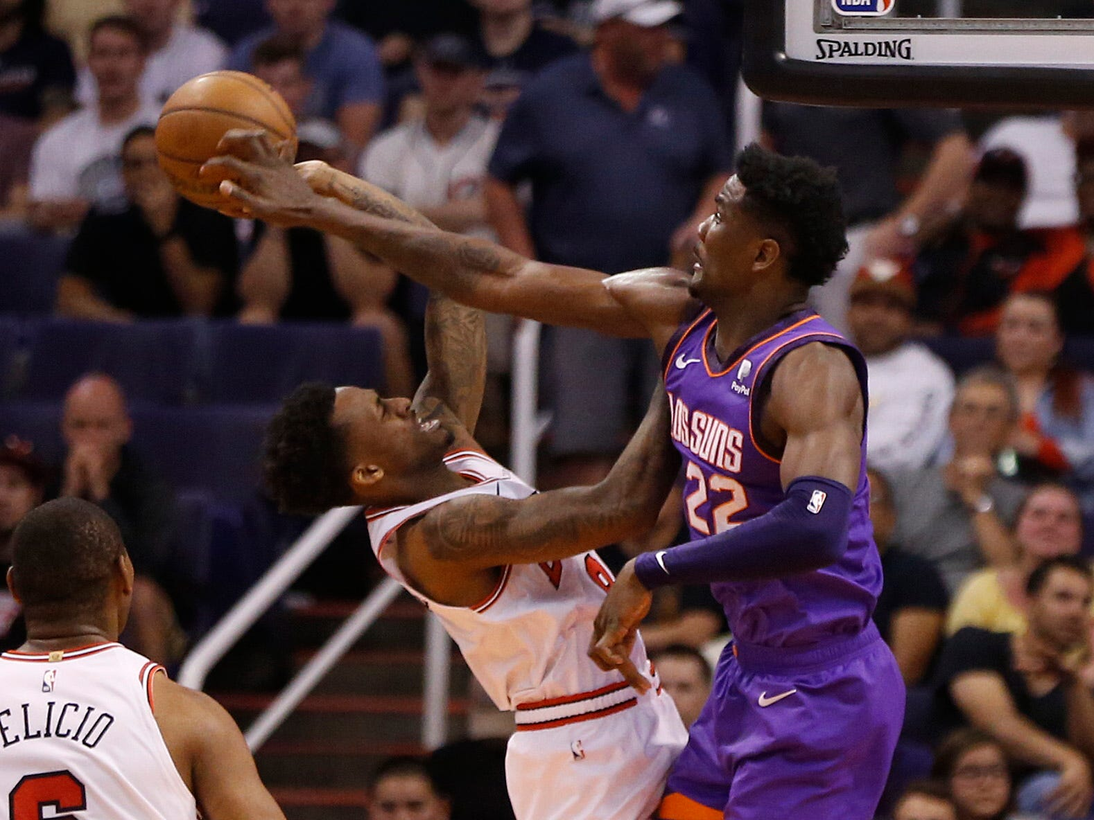 Suns' Deandre Ayton (22) blocks a shot against Bulls' Antonio Blakeney during the second half at Talking Stick Resort Arena in Phoenix, Ariz. on March 18, 2019.