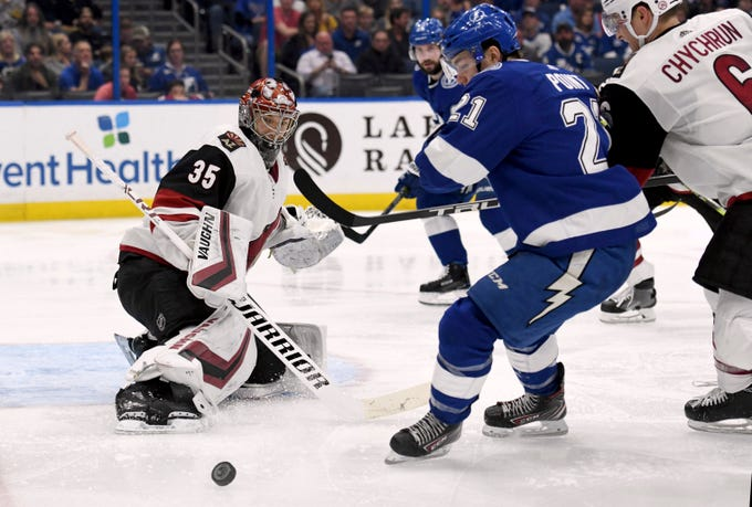 Arizona Coyotes goaltender Darcy Kuemper (35) deflects a shot as Tampa Bay Lightning center Brayden Point (21) looks for the rebound during the second period of an NHL hockey game Monday, March 18, 2019, in Tampa, Fla.