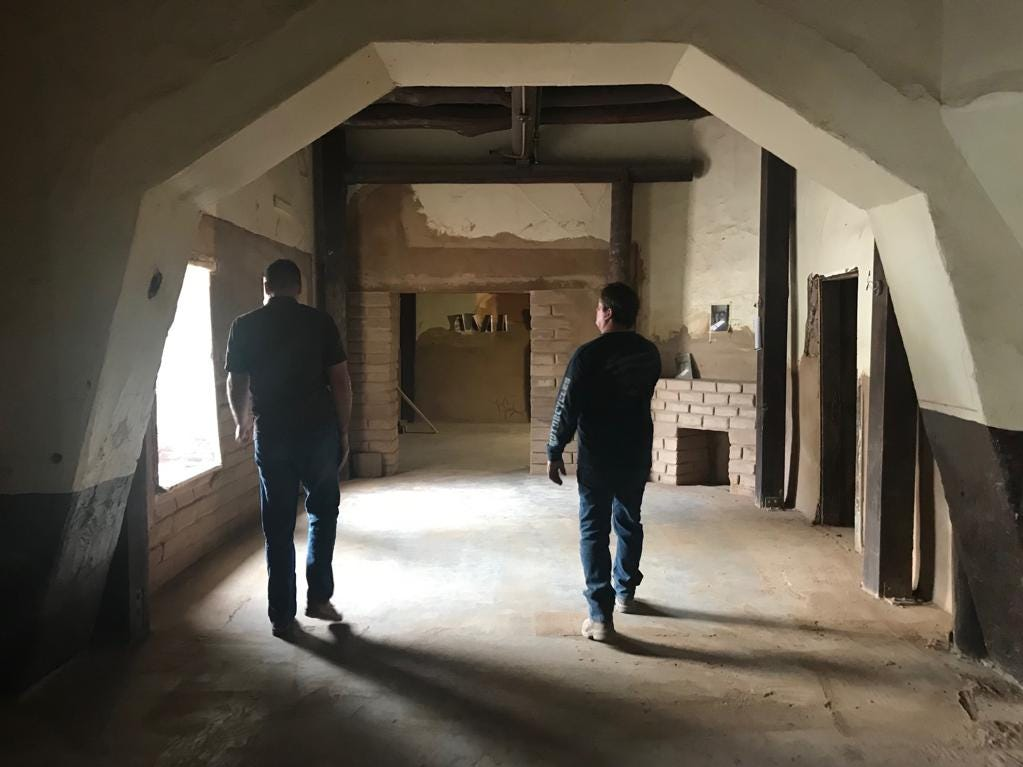 John Southard, Tempe's historic preservation officer, and adobe expert Reggie Mackay walk through the long room of the historic Hayden House.