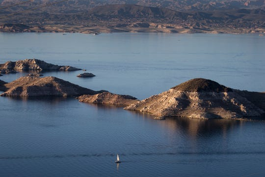 """A sailboat cruises past Rock Island March 17, 2019, in the Lake Mead National Recreation Area near the Arizona/Nevada border. A high-water mark or """"bathtub ring"""" is visible on the shoreline; Lake Mead is down 139 vertical feet."""