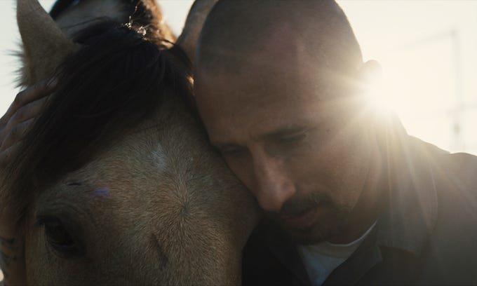 "Roman (Matthias Schoenaerts) is drawn to a horse in ""The Mustang."""