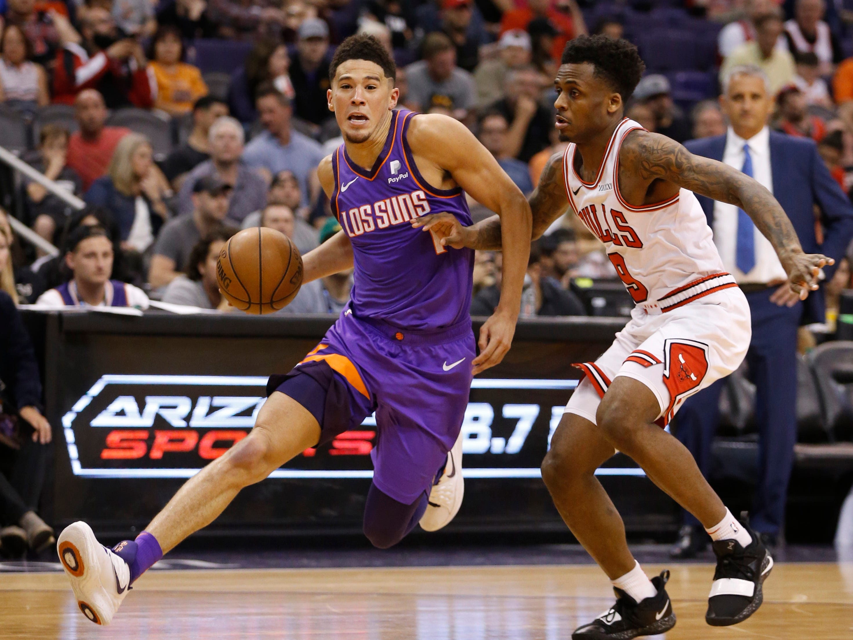 Suns' Devin Booker (1) drives past Bulls' Antonio Blakeney during the second half at Talking Stick Resort Arena in Phoenix, Ariz. on March 18, 2019.