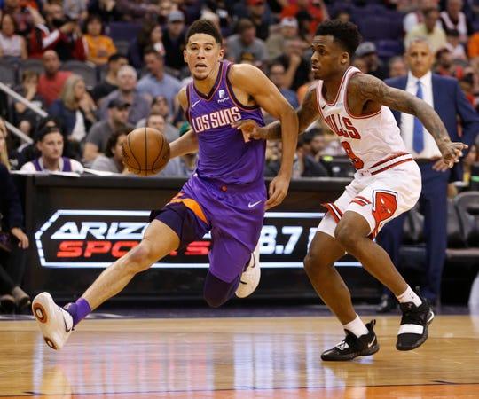 Suns' Devin Booker (1) drives past Bulls' Antonio Blakeney during the second half at Talking Stick Resort Arena in Phoenix, Ariz. on March 18, 2019.