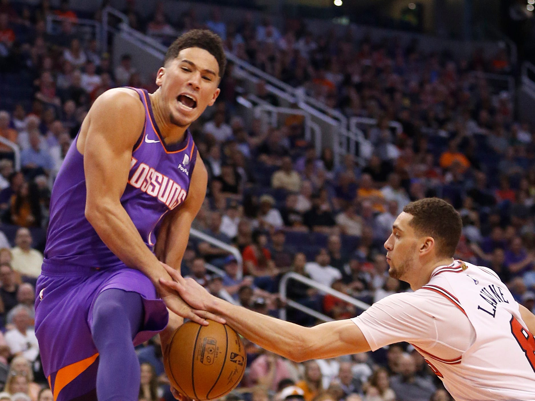 Bulls' Zach LaVine (8) strips the ball from Suns' Devin Booker (1) during the first half at Talking Stick Resort Arena in Phoenix, Ariz. on March 18, 2019.