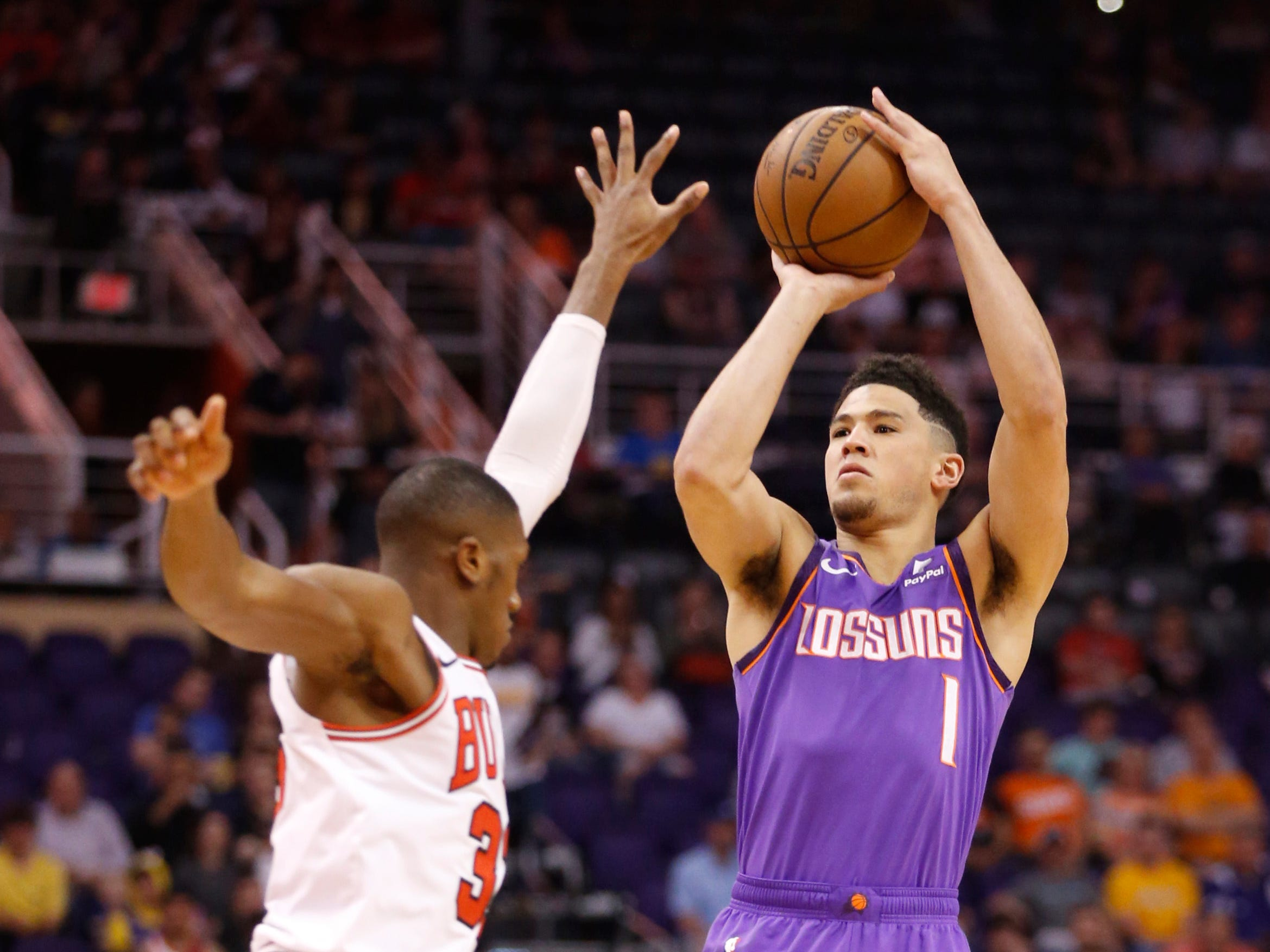 Suns' Devin Booker (1) shoots against Bulls' Kris Dunn (32) during the first half at Talking Stick Resort Arena in Phoenix, Ariz. on March 18, 2019.