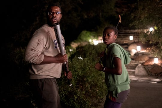 "Gabe (Winston Duke) and Zora (Shahadi Wright Joseph) protect themselves in ""Us."""
