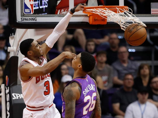 Chicago Bulls guard Shaquille Harrison dunks over Phoenix Suns forward Ray Spalding, right, during the first half of an NBA basketball game, Monday, March 18, 2019, in Phoenix. (AP Photo/Matt York)