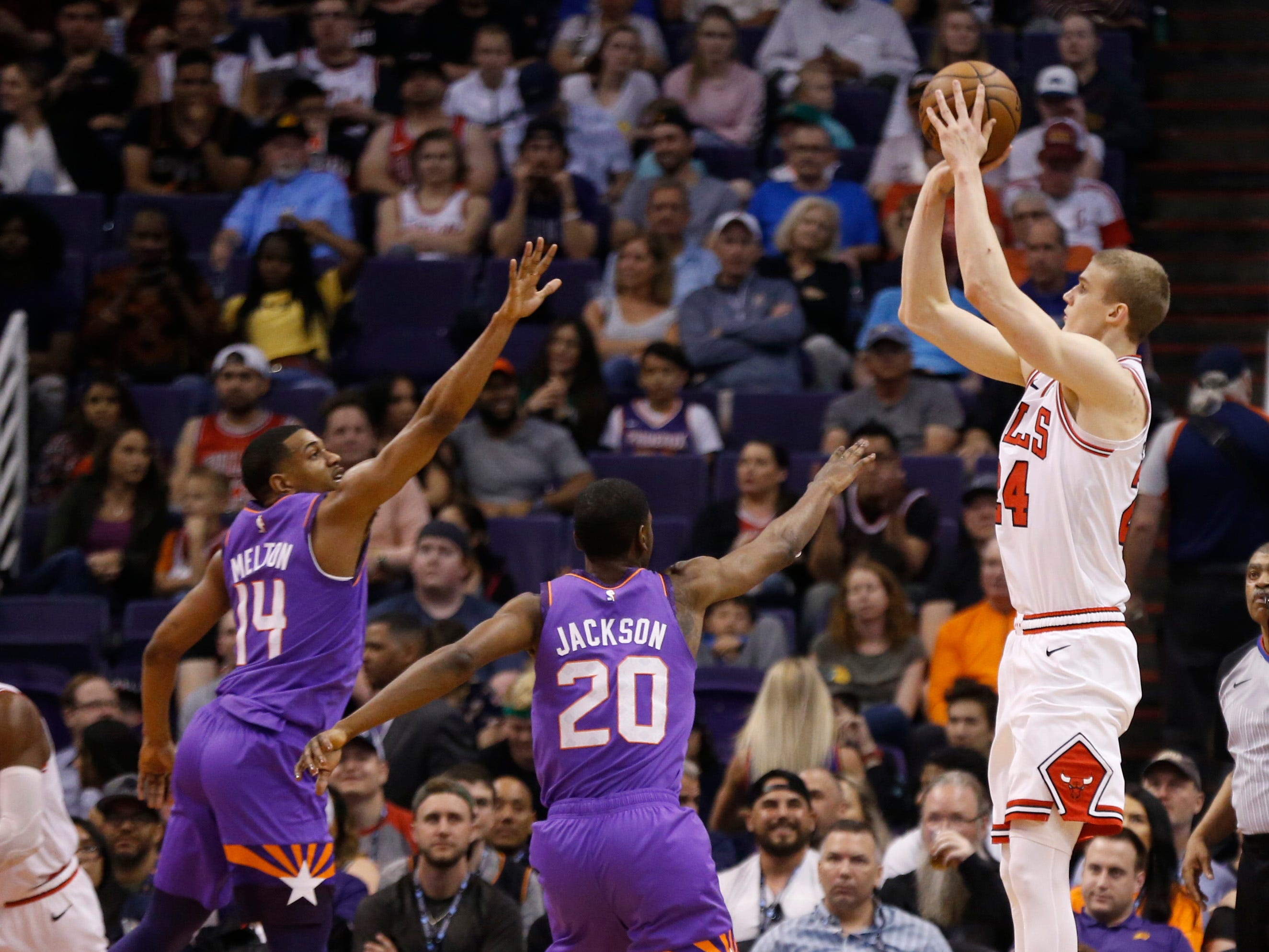 Bulls' Lauri Markanen (24) makes a shot against Suns' De'Anthony Melton (14) and Josh Jackson (20) during the second half at Talking Stick Resort Arena in Phoenix, Ariz. on March 18, 2019.