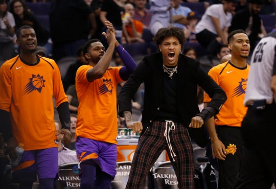 Suns' Kelly Oubre Jr. jumps up from the bench celebrating a basket against the Bulls during the second half at Talking Stick Resort Arena in Phoenix, Ariz. on March 18, 2019.