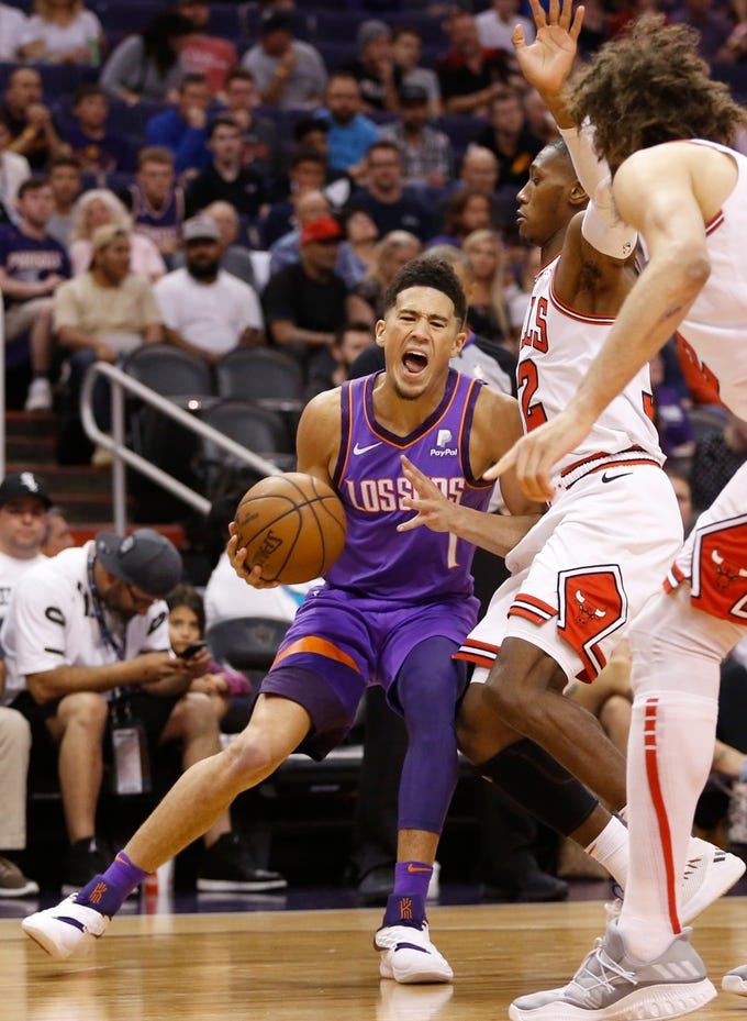 Suns' Devin Booker (1) draws a foul against Bulls' Kris Dunn (32) during the first half at Talking Stick Resort Arena in Phoenix, Ariz. on March 18, 2019.