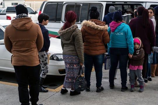 Migrantes solicitantes de asilo esperan ser transportados en Tijuana.
