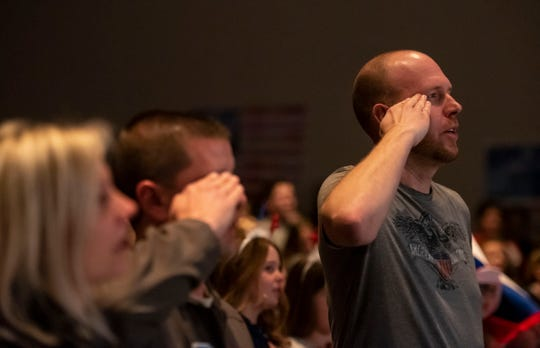 Algonquin Elementary PE teacher and U.S. Tech Sgt. Jeff Luts holds a salute as a choir composed of students sing the National Anthem Tuesday, March 19, 2019 in the school's auditorium. The students organized a surprise send-off ceremony for Luts, who will soon be deploying to an undisclosed location in the Middle East.