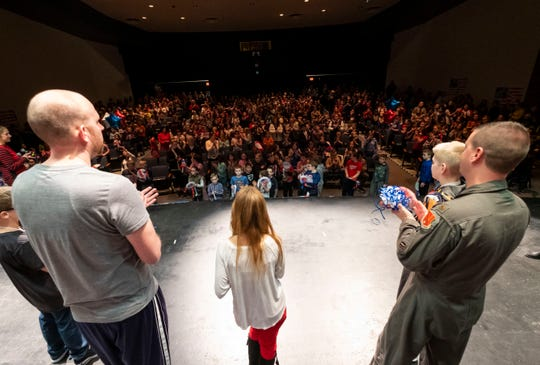 Algonquin Elementary PE teacher and U.S. Air Force Tech Sgt. Jeff Luts, left, stands on the stage in the school's auditorium in front of a theater full of students and faculty Tuesday, March 19, 2019 during a send-off ceremony organized by students. Luts, who has worked at the school for about two years, is being deployed to an undisclosed location in the Middle East.