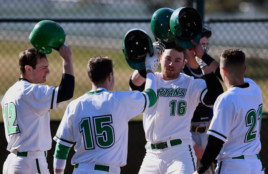Spartans teammates greet Justin Kilpatrick (16) after he hit his second home run of the game against Elizabethtown, Tuesday, March 19, 2019. Kilpatrick connected with a two-run homer in the second and at three-run shot in the third.
