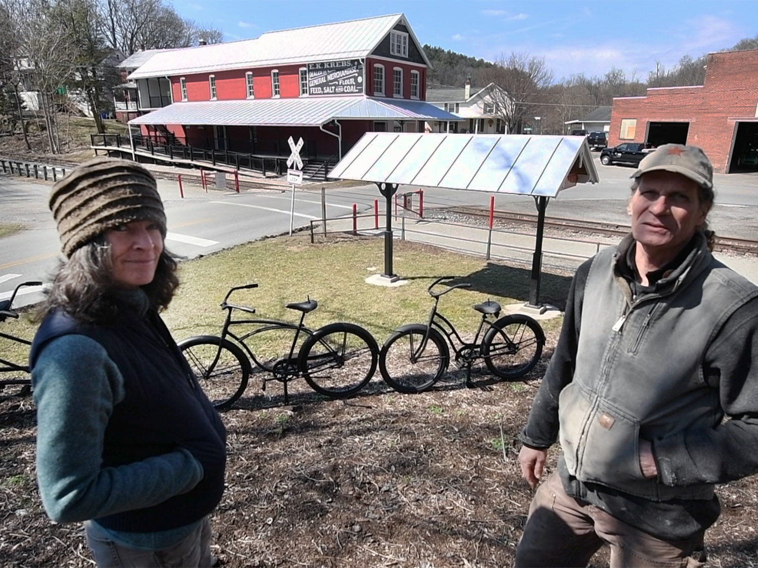 Ellen Darby, left, and David Keller stand with the restorations they have made to Seitzland Village, outside of Glen Rock, behind them. The exterior of the store in the background was restored with new porches, the store front rebuilt and a train station was added. The York County Heritage Rail Trail runs in the background.