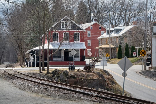 The York County Heritage Rail Trail curves in front of the Seitzland store. The stone building, at right, is also under renovation by Ellen Darby, left, and David Keller. The former Seitzland Hotel building is at center.
