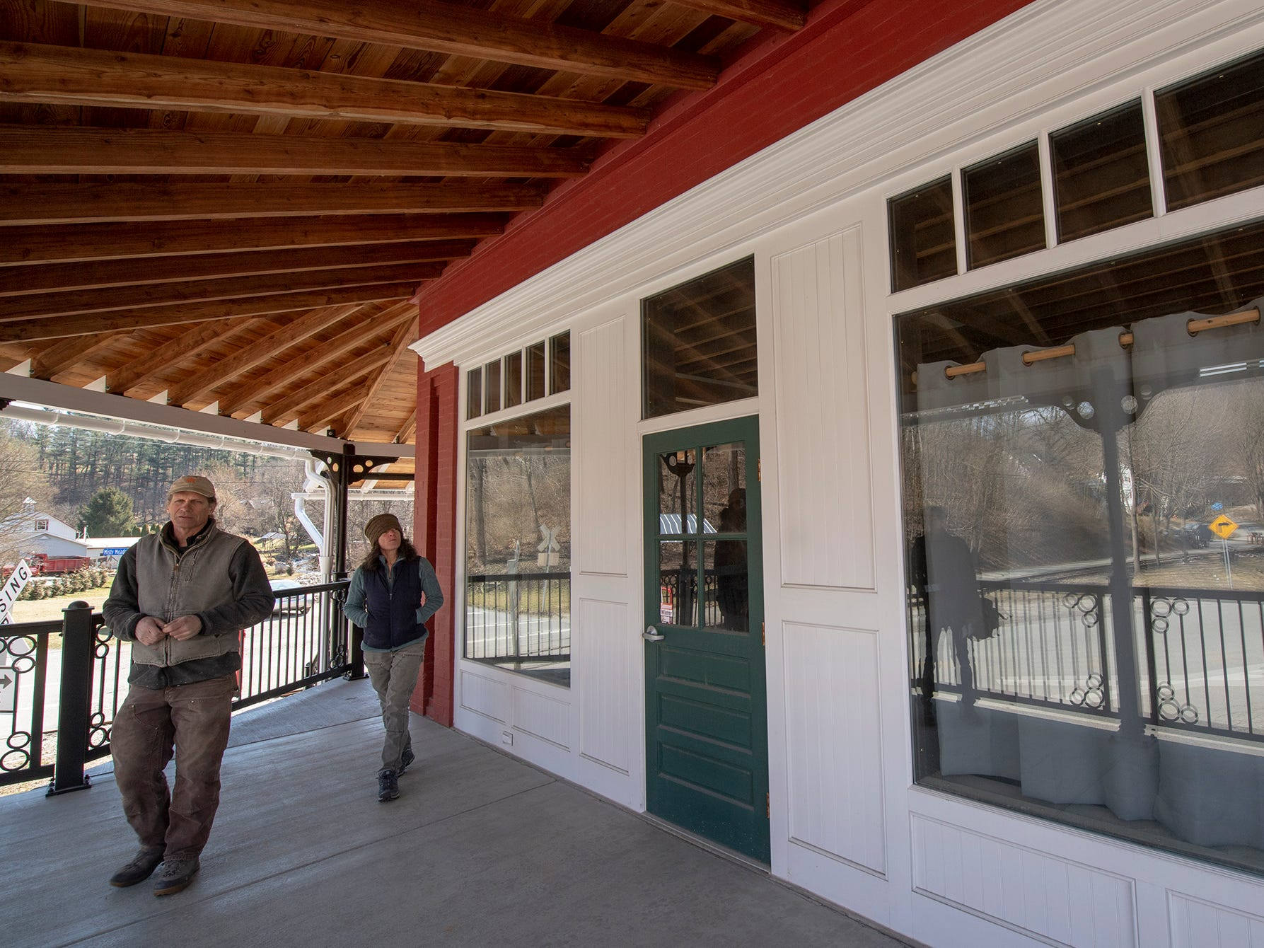 David Keller, left, and Ellen Darby walk on the porch of the   Seitzland store. The storefront was rebuilt, even replacing brick pillars. The larch pine used in the porch timbers will remain unpainted and age naturally. It was sawmill cut, carpenter bees won't bother it and it is strong enough to be milled in the original dimensions that would have appeared on a porch in 1915.