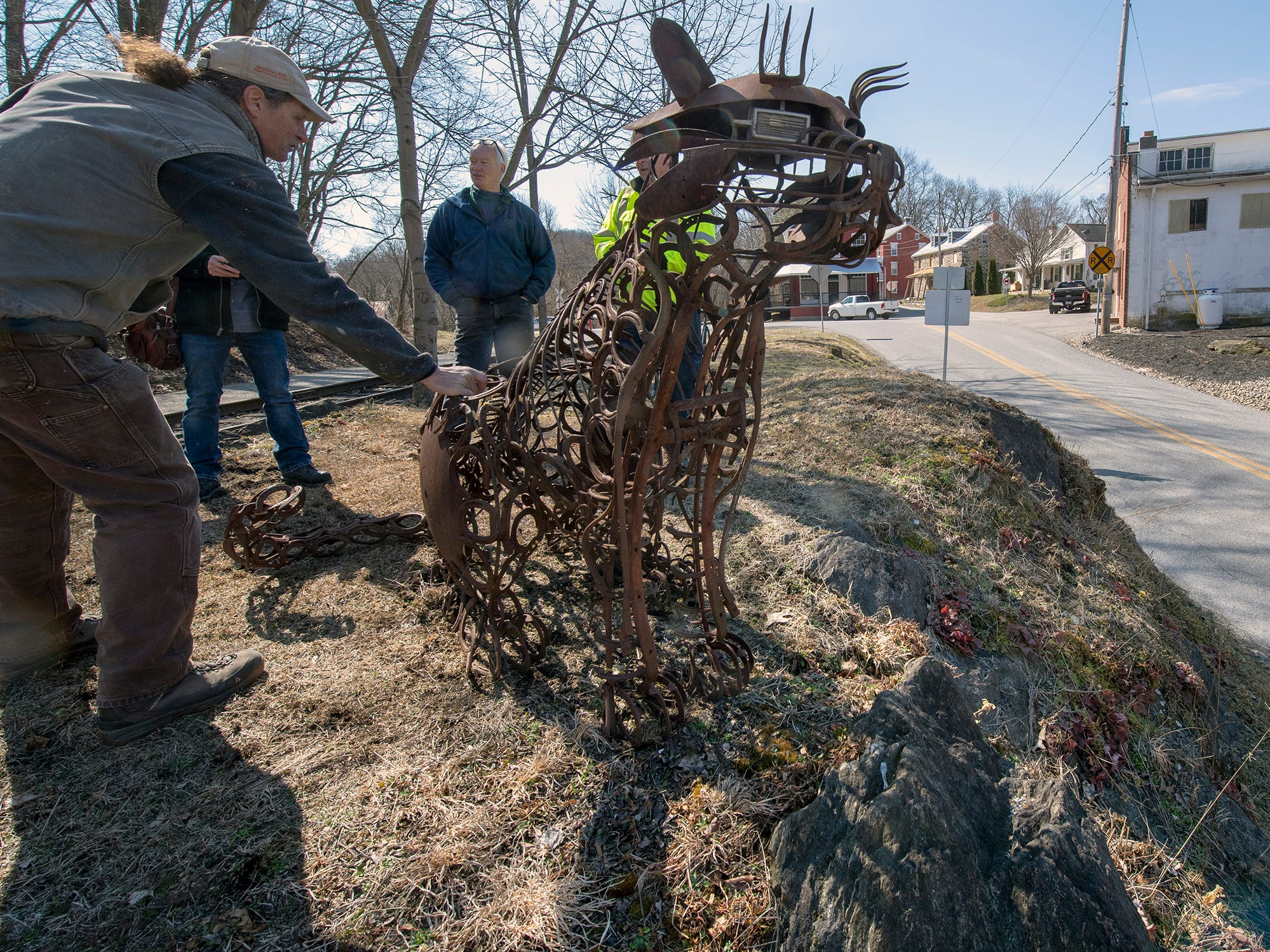 David Keller, left, is with a large cat sculpture that was installed in Seitzland overlooking the road approaching from Glen Rock.