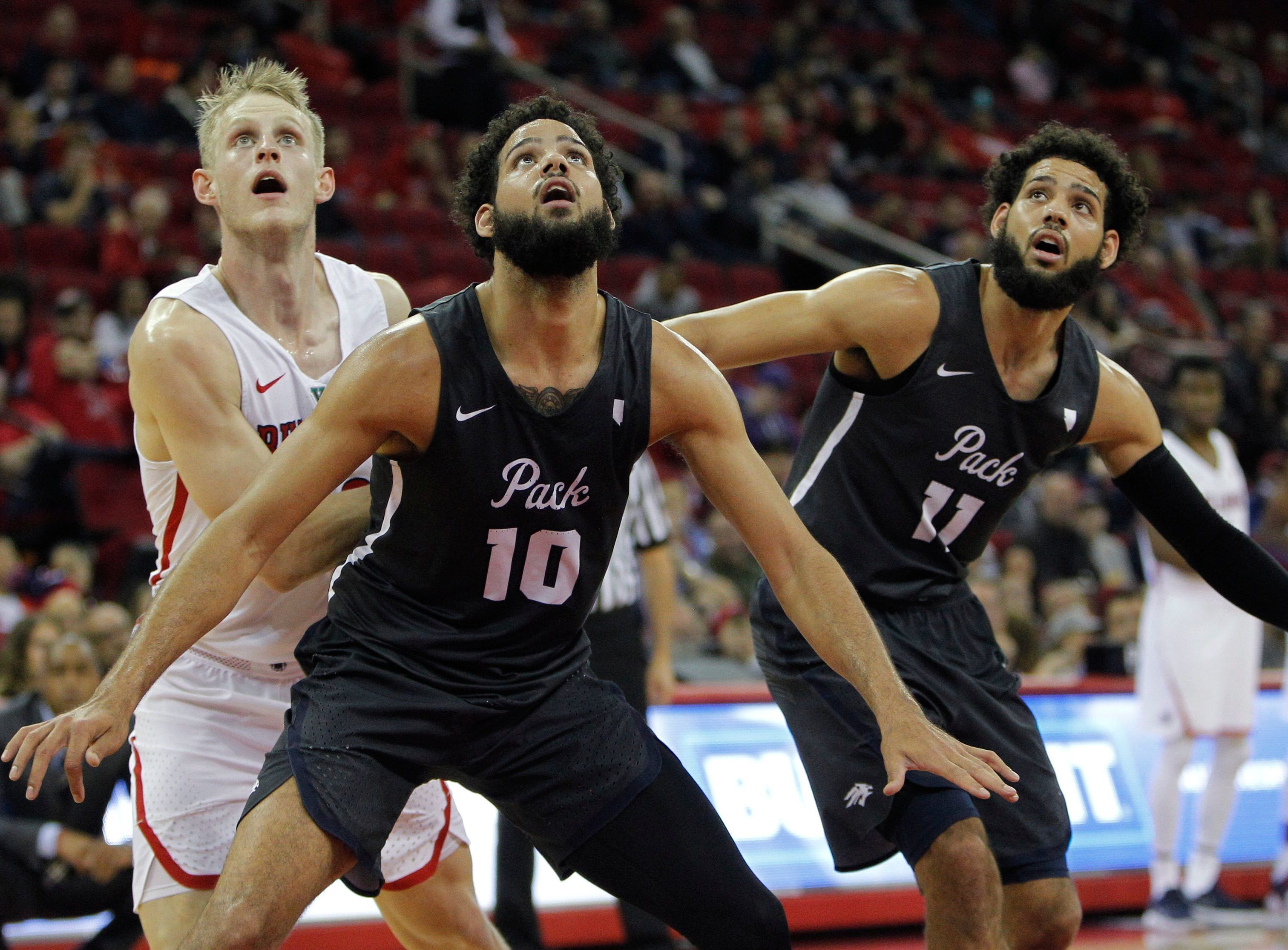 Nevada's Caleb Martin, left, and Cody Martin box out for a rebound against Fresno State's Sam Bittner.