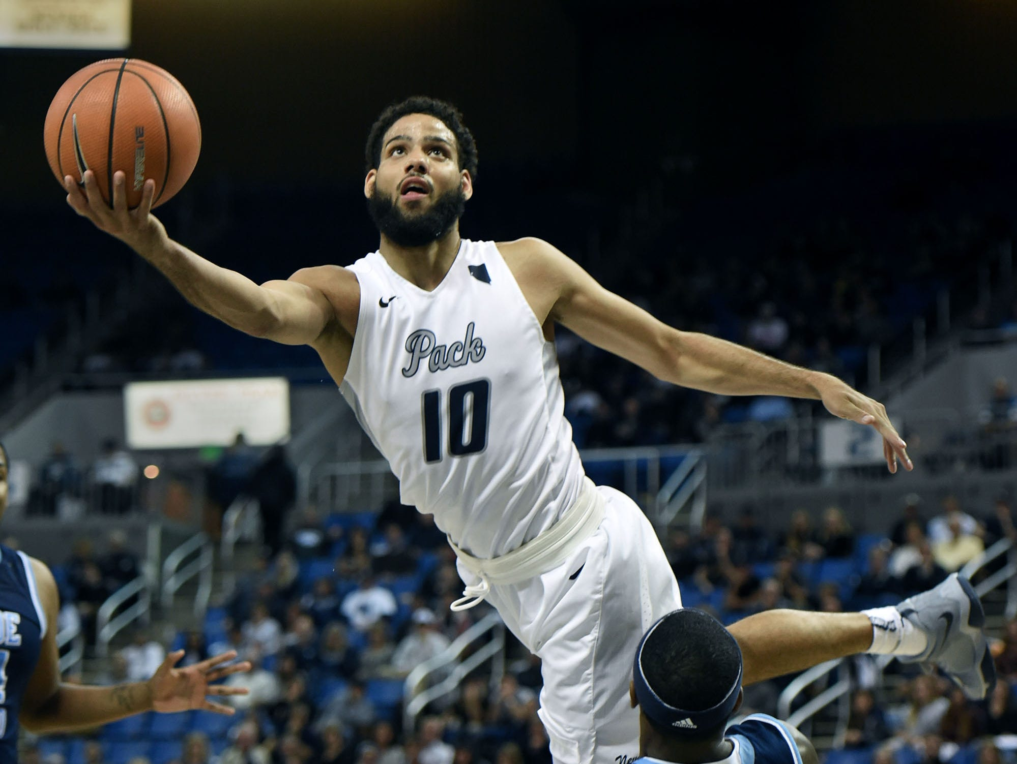 Nevada's Caleb Martin goes over Rhode's Jarvis Garrett to score in the second half of Monday's game at Lawlor Events Center on Nov. 13, 2017. Nevada won 88-81.