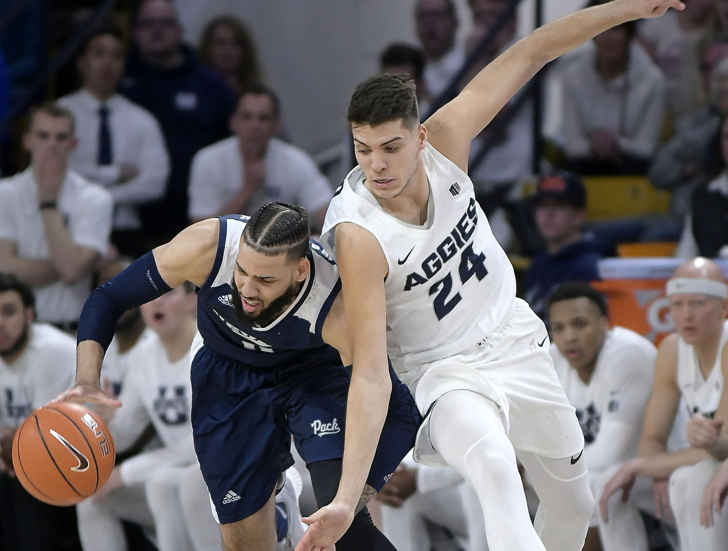 Nevada forward Cody Martin (11) gets fouled by Utah State guard Diogo Brito (24) during an NCAA college basketball game Saturday, March 2, 2019, in Logan, Utah.