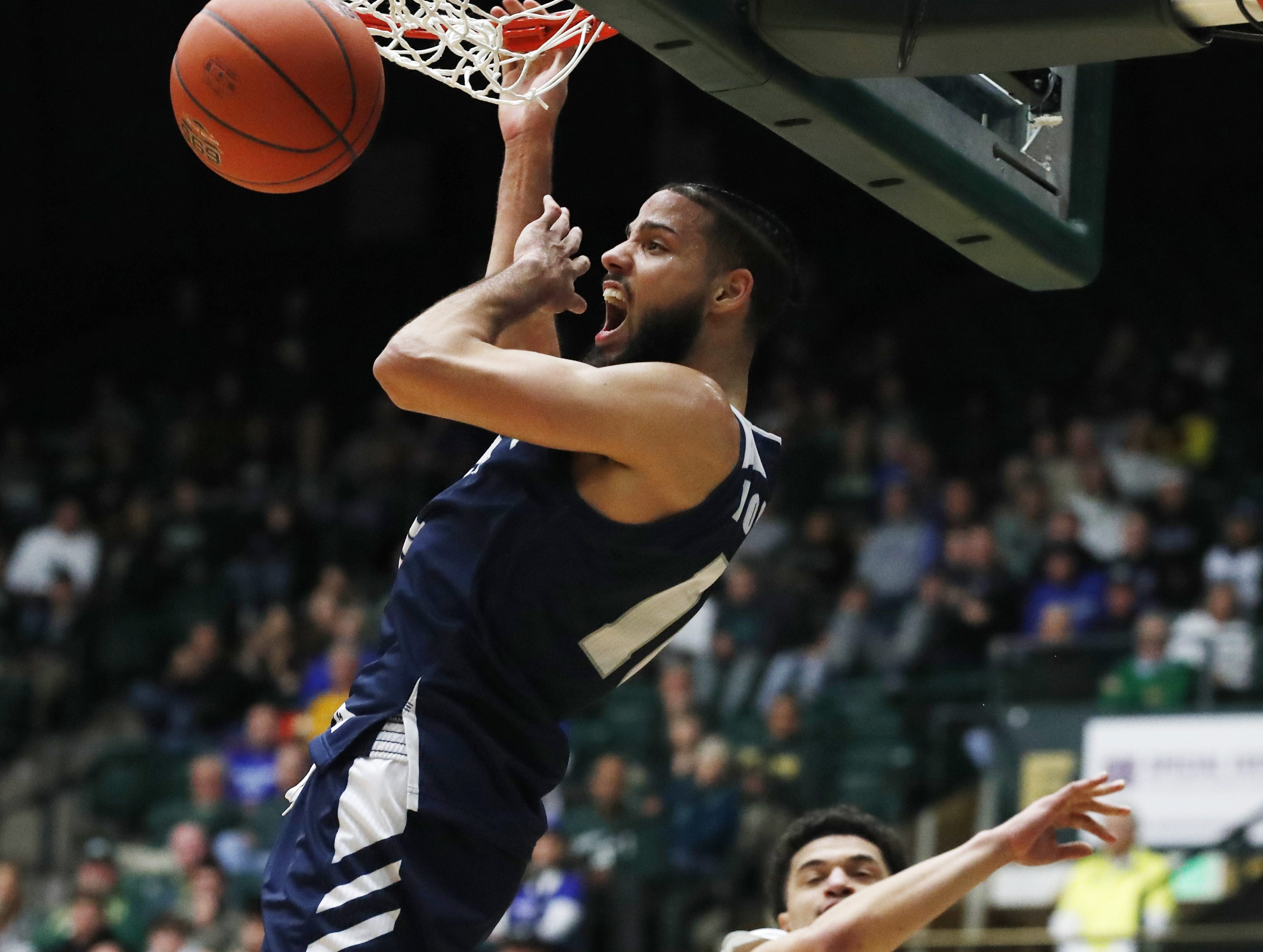 Nevada forward Caleb Martin dunks next to Colorado State guard Anthony Masinton-Bonner during the second half of an NCAA college basketball game Wednesday, Feb. 6, 2019, in Fort Collins, Colo. Nevada won 98-82.