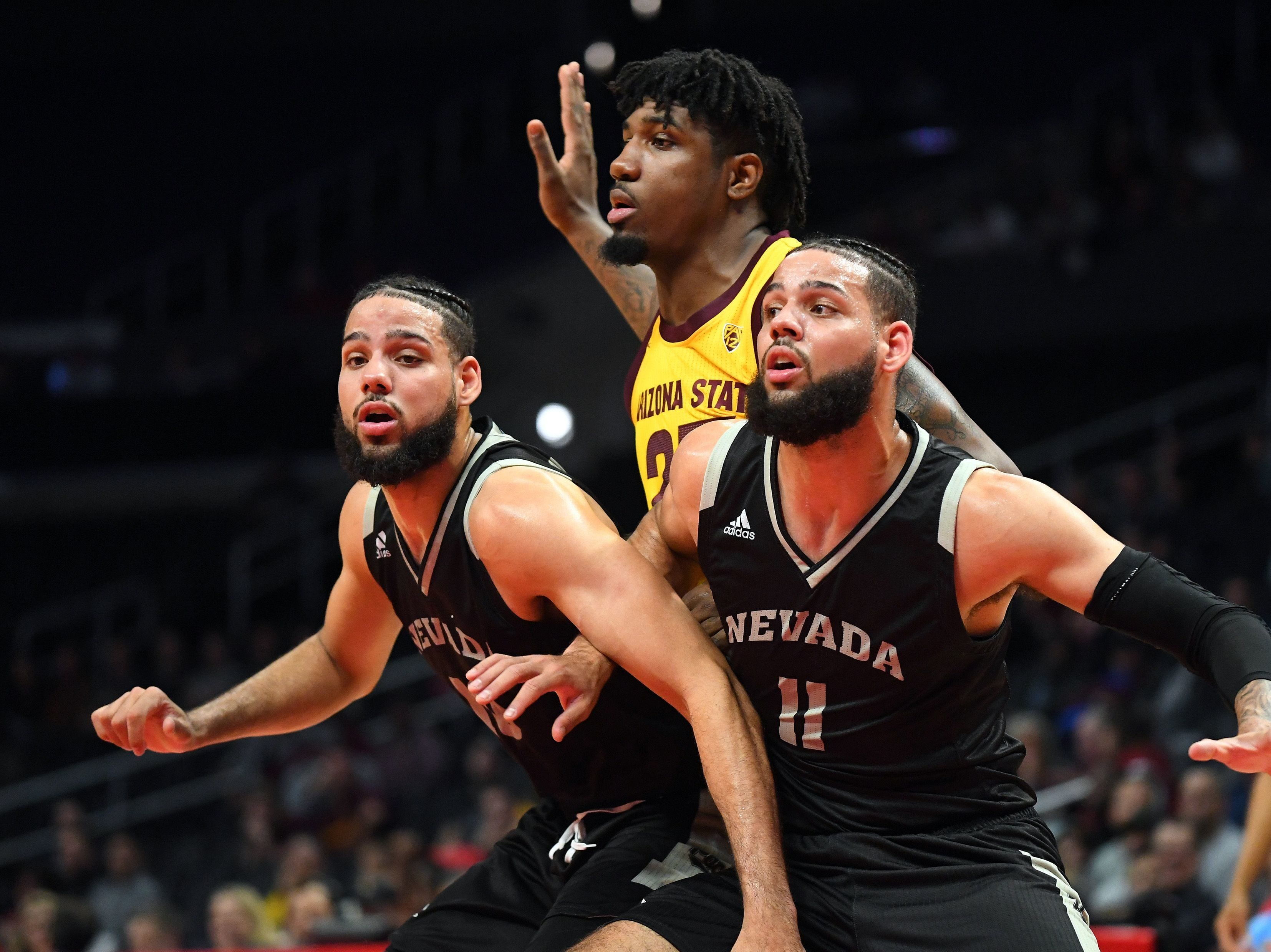 Nevada Wolf Pack forward Cody Martin (11) and forward Caleb Martin (10) box out Arizona State Sun Devils forward Romello White (23) under the basket in the first half of the game at Staples Center.