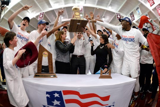 Colgate coach Matt Langel, center, lifts the trophy after the team's NCAA college basketball game against Bucknell for the championship of the Patriot League.