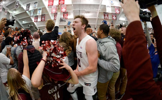 Colgate forward Will Rayman, center, celebrates as fans rush the court after Colgate defeated Bucknell 94-80 in the Patriot League championship game.