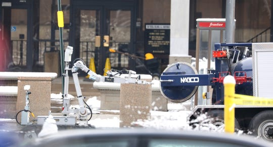 Rochester Police Department's bomb squad robot removes a suspicious package from in front of the Federal Building in downtown Rochester Monday morning, March 19, 2019.