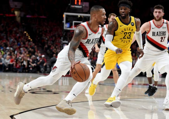 Portland Trail Blazers guard Damian Lillard, left, drives to the basket on Indiana Pacers guard Wesley Matthews, right, during the second half of an NBA basketball game in Portland, Ore., Monday, March 18, 2019. The Blazers won 106-98.