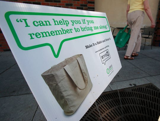A customer walks into a grocery store in front of an advertisement for cloth bags. The sign is helping remind shoppers to form a habit of bringing their reusable bags with them when they shop.