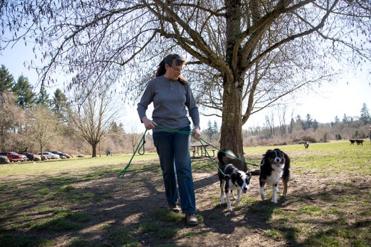 Jane Sommers walks her dogs Portia and Zoe at Minto-Brown Park in Salem on March 18, 2019.