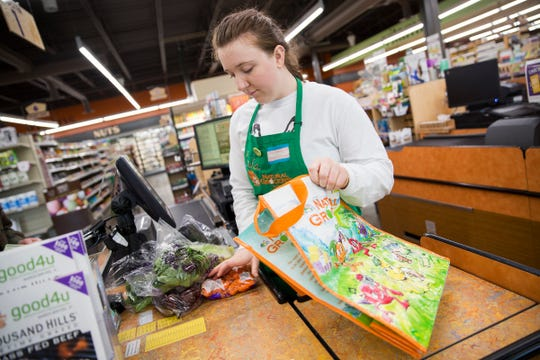 Erika Graves bags groceries in a reusable bag at Natural Grocers in Salem on March 18, 2019.