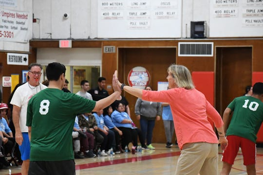 North Salinas Athletic Director Jean Ashen high-fives an Alisal player for scoring a basket.