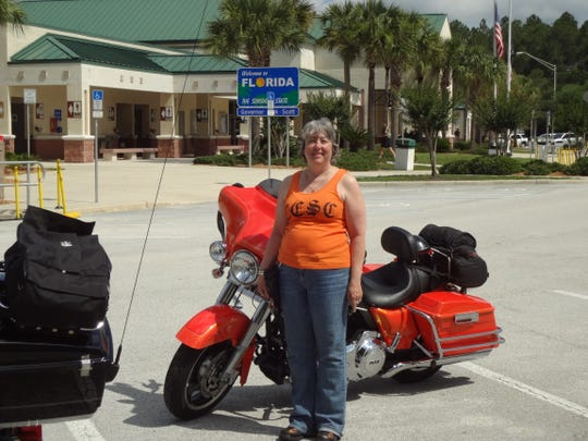 "Lizzie ""Liz"" Yontz of Wallops Island on Virginia's Eastern Shore stands with her 2012 Harley-Davidson Street Glide."