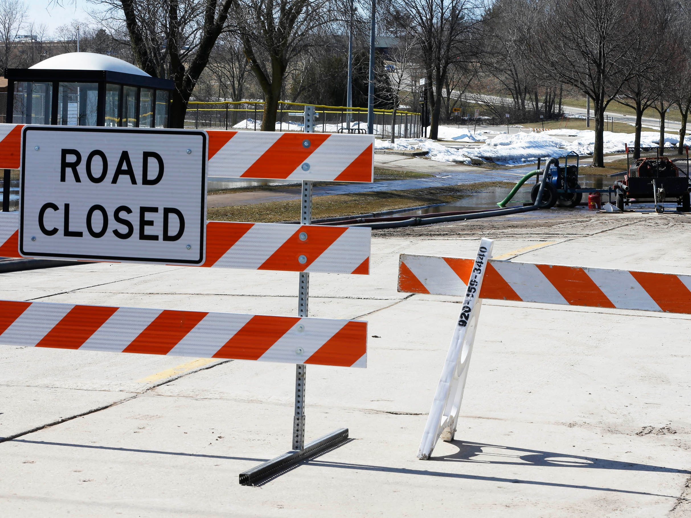 A section of New Jersey Avenue is closed to traffic while pumps work to remedy flooding on the street, Tuesday, March 19, 2019, in Sheboygan, Wis.
