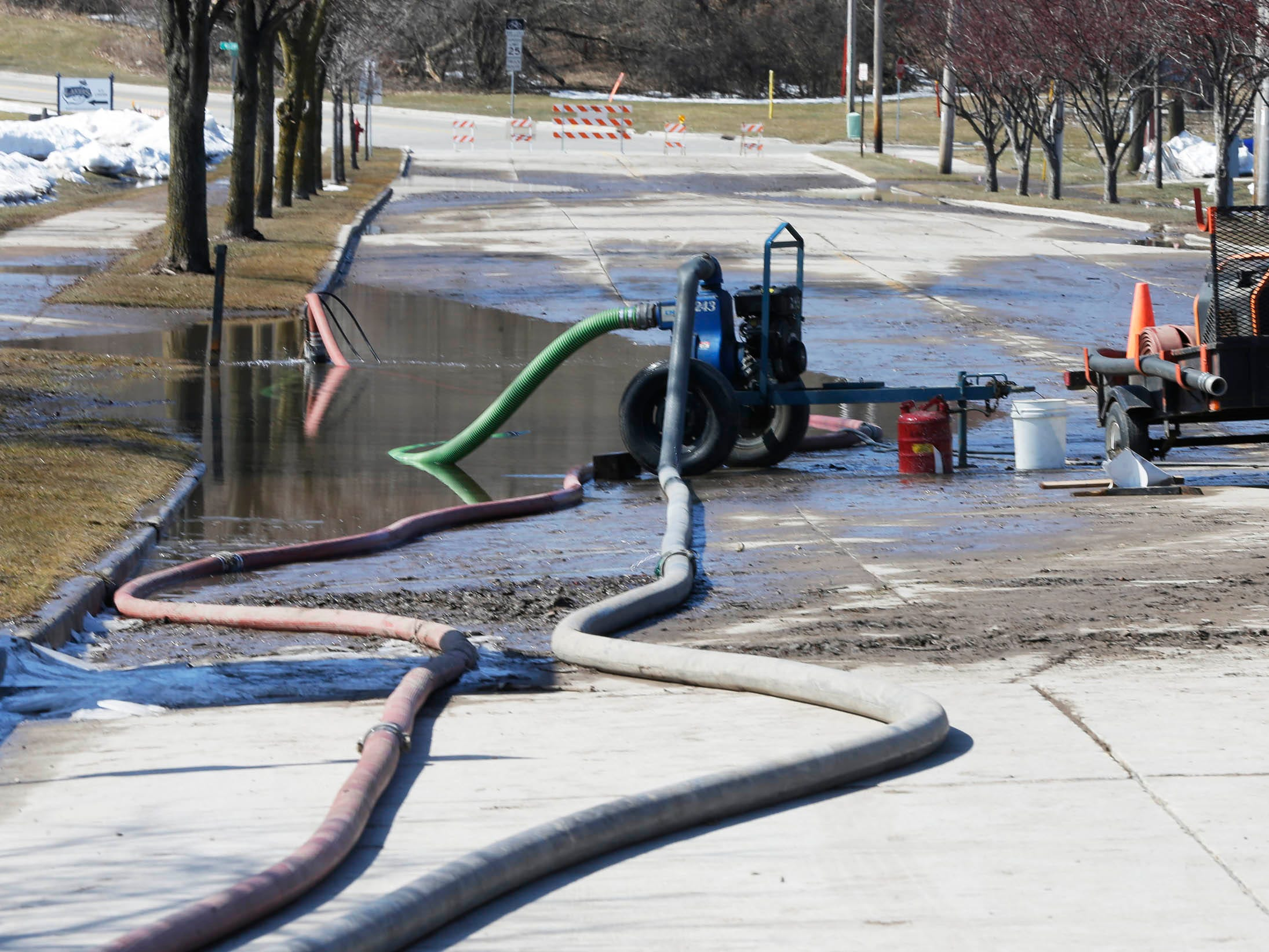 Two pumps work to move the water that is flooding New Jersey Avenue, Tuesday, March 19, 2019, in Sheboygan, Wis.