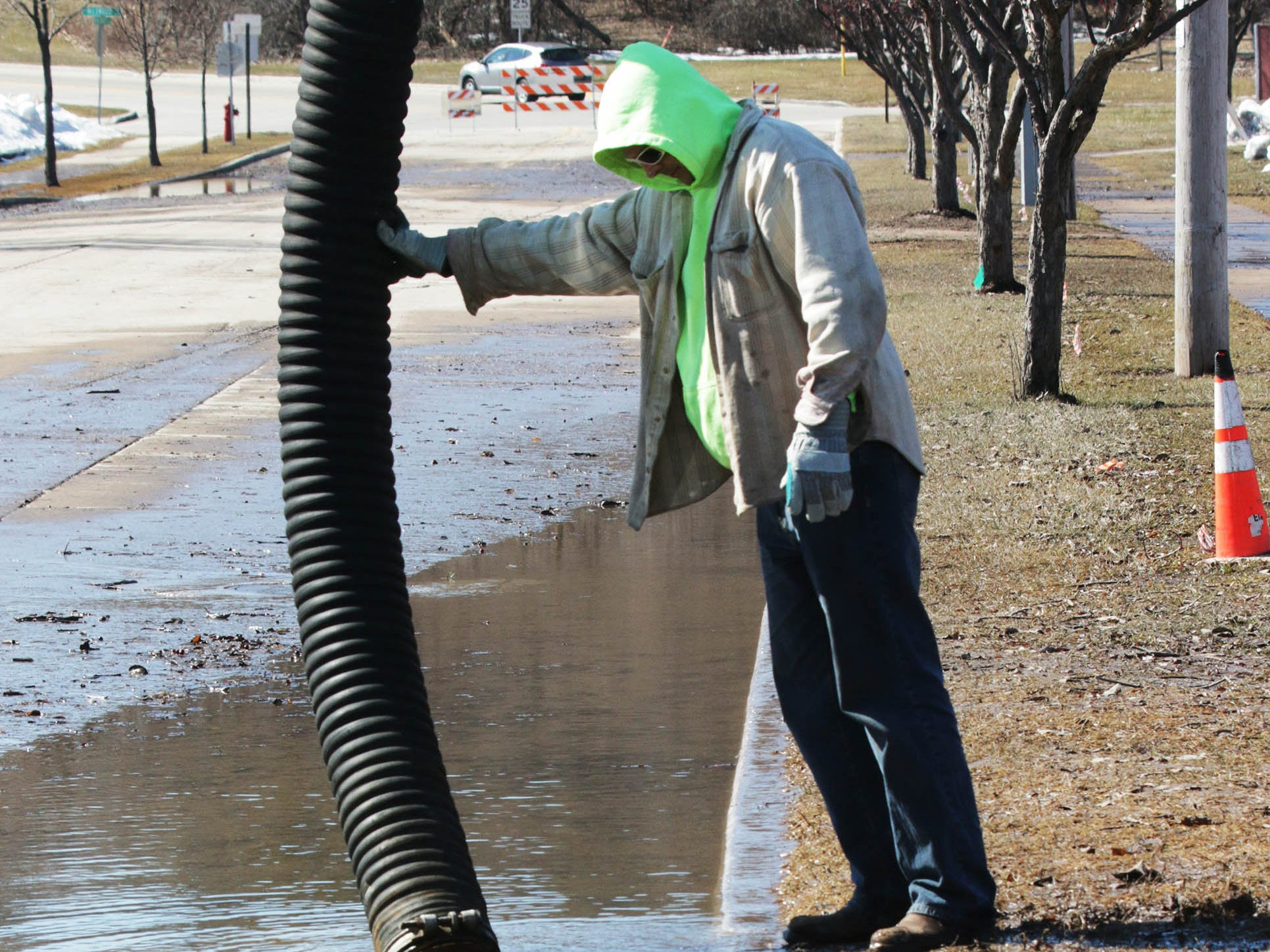 Department of Public works employee Ken Meinert is reflected with the suction pipe of a sewer jet, Tuesday, March 19, 2019, in Sheboygan, Wis. A city employee said they are hoping to have the street open in the next day.