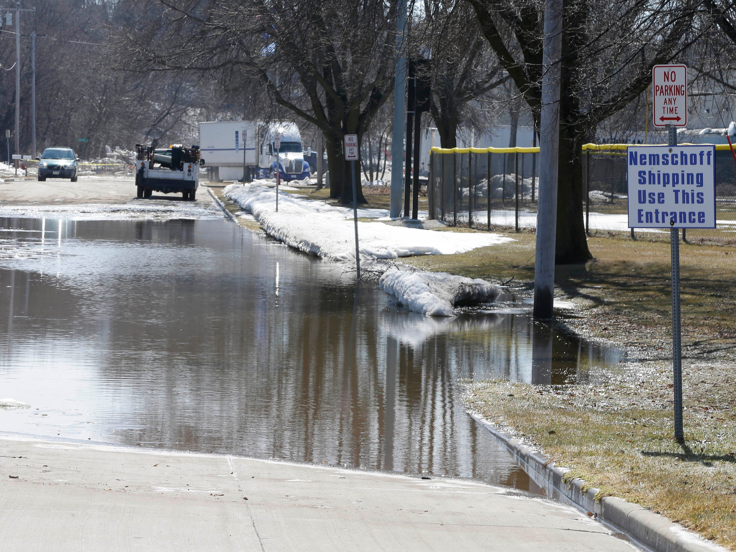 North 22nd Street is flooded south of New Jersey Avenue, Tuesday, March 19, 2019, in Sheboygan, Wis. The street leads to Nemschoff which has had to have employees park at an alternate location.