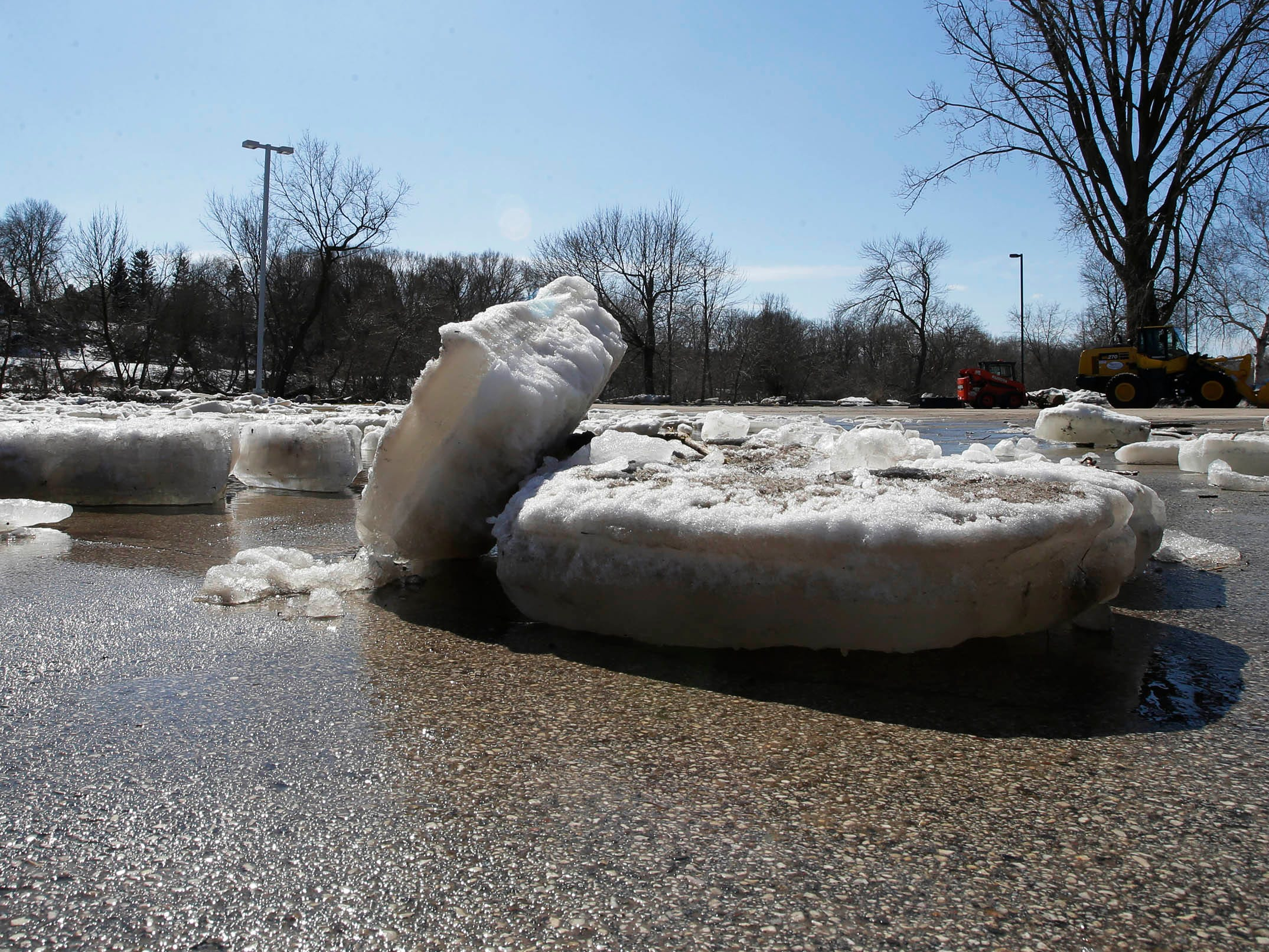 Huge slabs of ice cover the parking lot at Nemschoff, Tuesday, March 19, 2019, in Sheboygan, Wis.