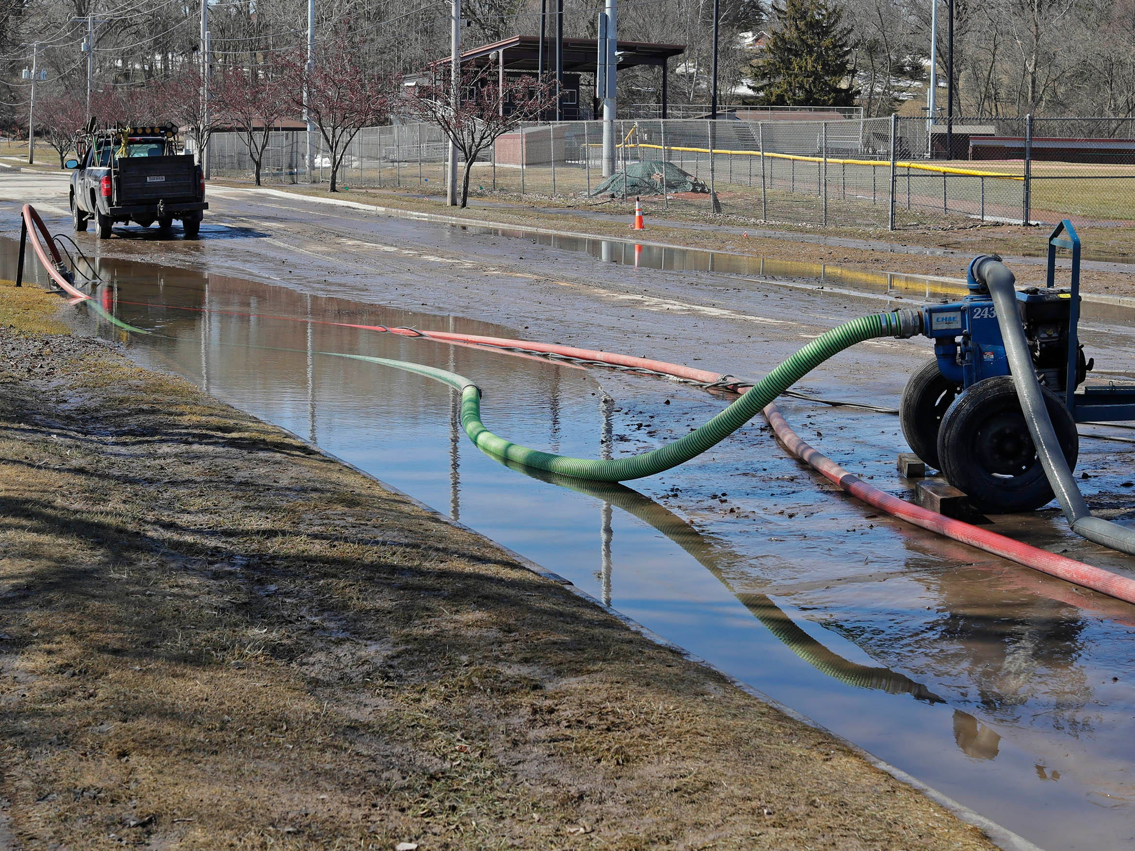 Portable pumps work on moving water to clear catch basins along New Jersey Avenue, Tuesday, March 19, 2019, in Sheboygan, Wis.