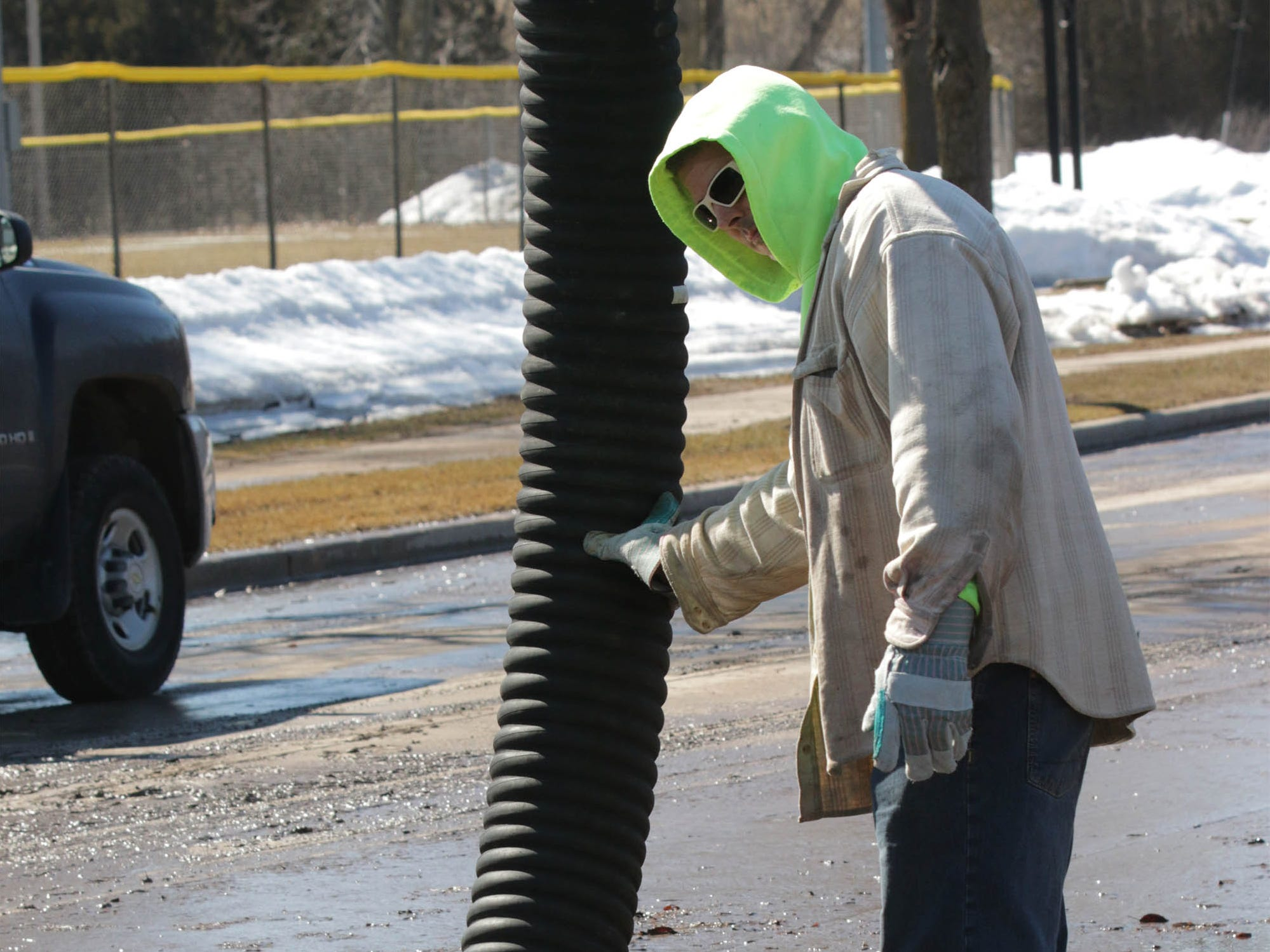 Department of Public works employee Ken Meinert controls the suction pipe of a sewer jet, Tuesday, March 19, 2019, in Sheboygan, Wis. A city employee said they are hoping to have the street open in the next day.