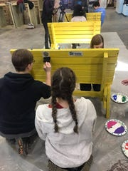 New Technology High School students paint benches in February to give to elementary schools as part of a community service project with Greater Sioux Falls Habitat for Humanity. The benches will be delivered in April.